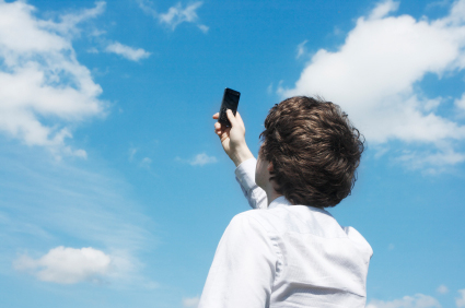 Man with phone in hand pointing to cloudy sky