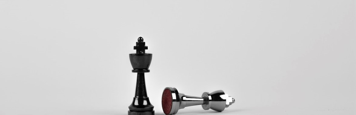 Chess pieces with one knocked over