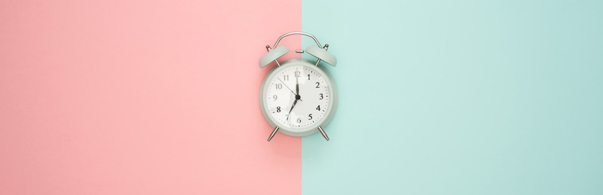 Alarm clock on pink and green wall