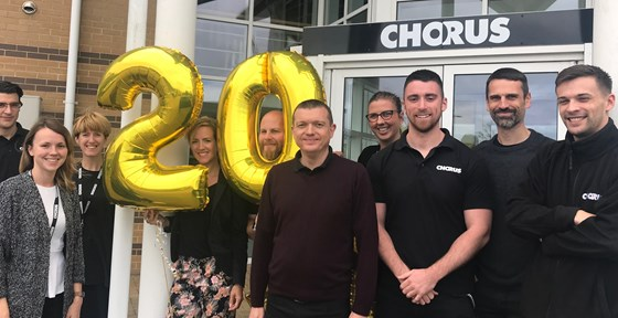 Staff in front of Chorus entrance with 20-year balloons