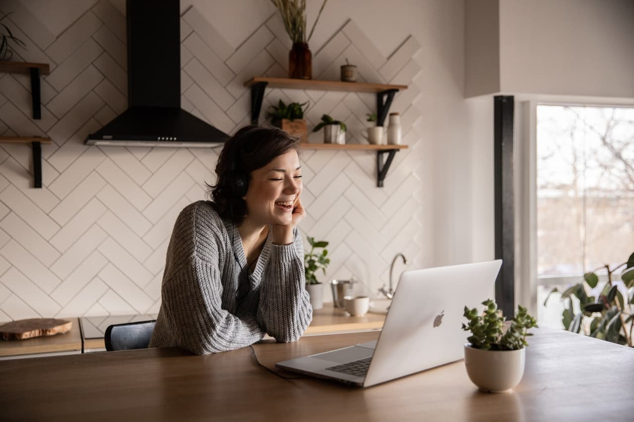 Woman laughing at kitchen table by laptop