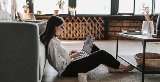 Woman working on laptop in lounge
