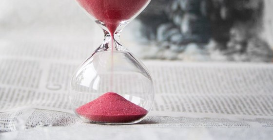 Pink sand timer on newspapers